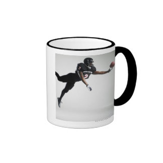 Football player leaping in mid air to catch ball coffee mugs