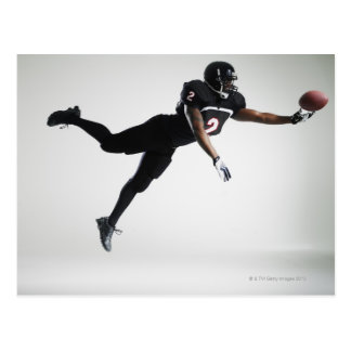 Football player leaping in mid air to catch ball postcard