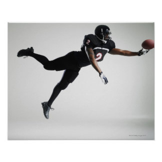 Football player leaping in mid air to catch ball poster