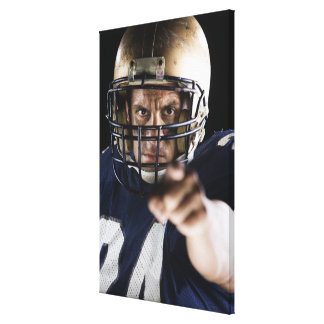 Football player pointing and looking intense canvas print