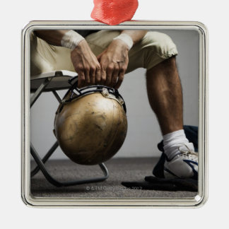 Football player sitting in locker room christmas ornament