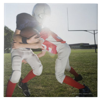 Football player tackling opponent tile
