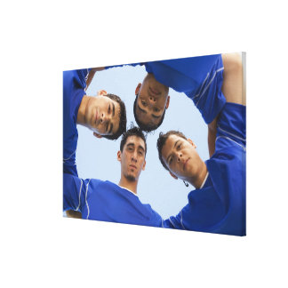 Football players huddled together canvas print