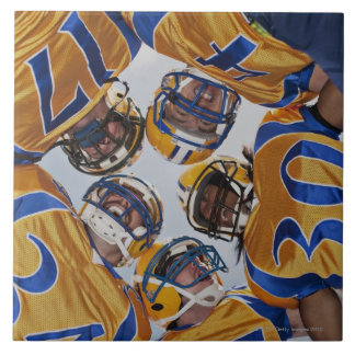 Football players in huddle tile