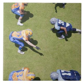 Football players playing football tile