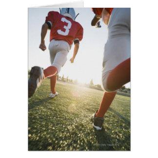 Football players running on field card