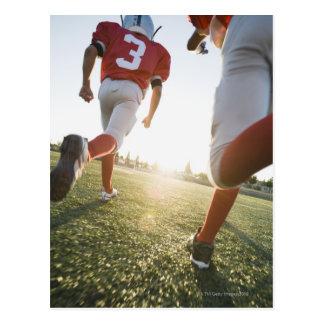 Football players running on field postcard