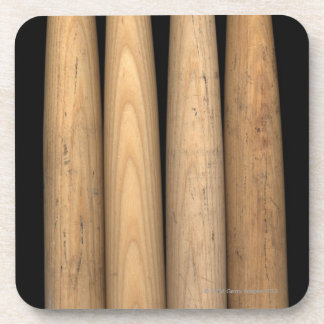 Four old baseball bats on black background coaster