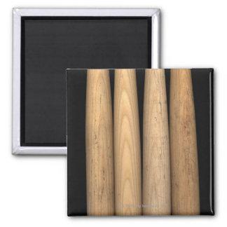 Four old baseball bats on black background magnet