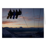 Four snowboarders are silhouetted on a ski lift