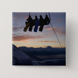 Four snowboarders are silhouetted on a ski lift 15 cm square badge