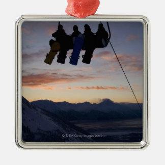 Four snowboarders are silhouetted on a ski lift christmas ornament