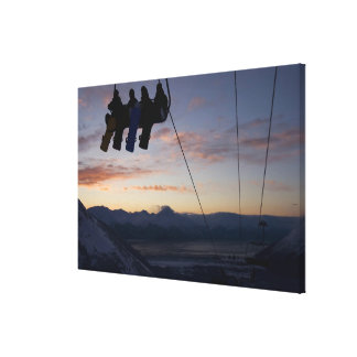 Four snowboarders are silhouetted on a ski lift gallery wrapped canvas