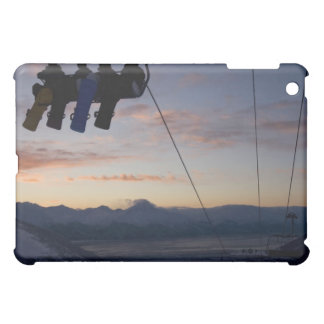 Four snowboarders are silhouetted on a ski lift iPad mini covers