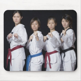 Four young women standing in punching position mouse pad