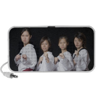 Four young women standing in punching position portable speakers