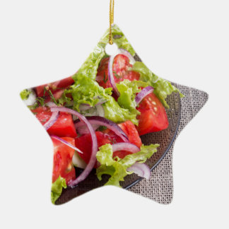 Fragment of a transparent plate with a fresh salad christmas ornament