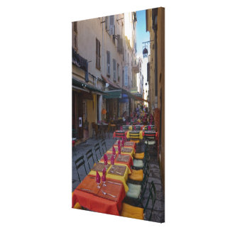 France, Corsica. Tables of cafe set up in narrow Stretched Canvas Prints