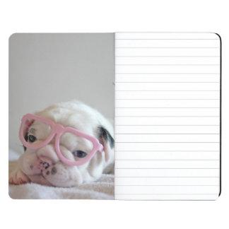 French bulldog white cub Glasses, lying on white Journal