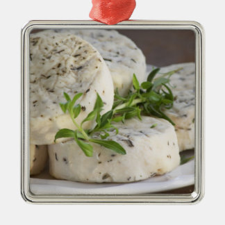 French goat cheese - chevre - with herbs on a Silver-Colored square decoration