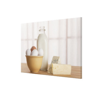 Fresh eggs cheese and milk on counter canvas print