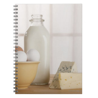 Fresh eggs cheese and milk on counter notebook