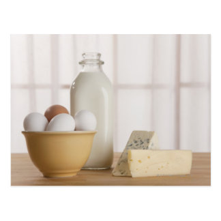Fresh eggs cheese and milk on counter postcards