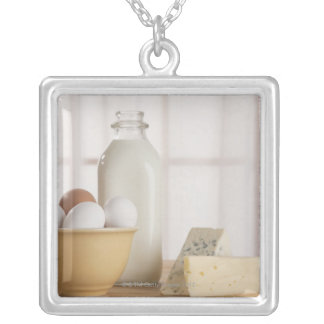 Fresh eggs cheese and milk on counter silver plated necklace