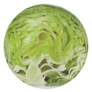 Fresh iceberg lettuce cut in half, on white plate