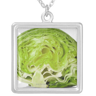 Fresh iceberg lettuce cut in half, on white silver plated necklace
