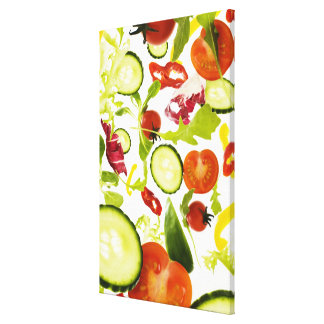 Fresh mixed salad vegetables falling to camera canvas print