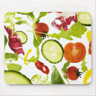 Fresh mixed salad vegetables falling to camera mouse mat