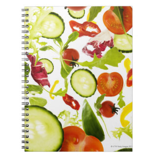 Fresh mixed salad vegetables falling to camera notebook