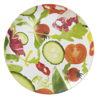 Fresh mixed salad vegetables falling to camera plate