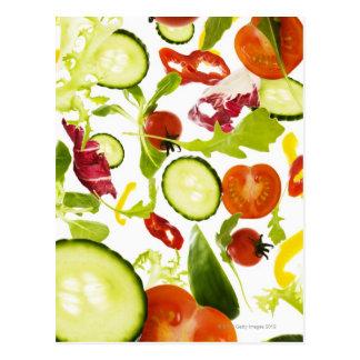 Fresh mixed salad vegetables falling to camera postcard