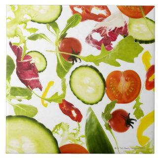 Fresh mixed salad vegetables falling to camera tile