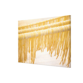Freshly made pasta drying on a wooden rack canvas print