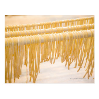 Freshly made pasta drying on a wooden rack postcard