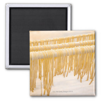 Freshly made pasta drying on a wooden rack square magnet