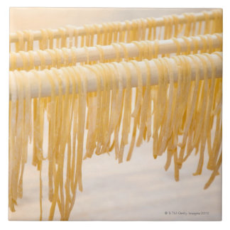 Freshly made pasta drying on a wooden rack tile