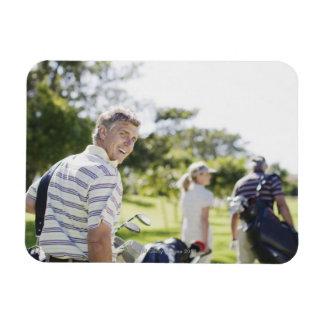 Friends carrying golf bags rectangular photo magnet