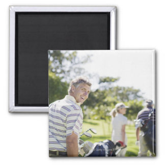 Friends carrying golf bags square magnet