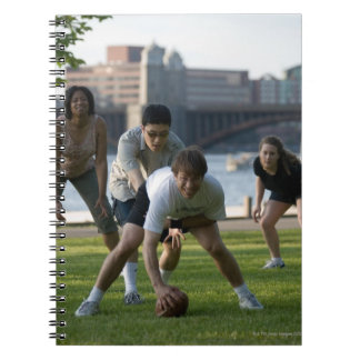 Friends playing game of football note books