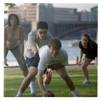 Friends playing game of football tile
