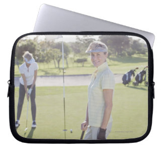 Friends playing golf laptop sleeves