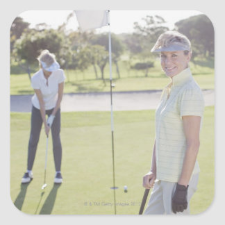 Friends playing golf square sticker