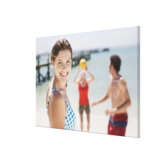 Friends playing volleyball at beach canvas print