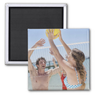 Friends playing volleyball on beach square magnet