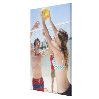 Friends playing volleyball on beach stretched canvas prints