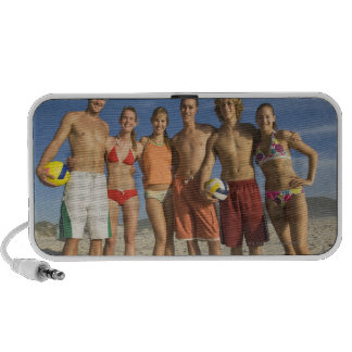 Friends posing on beach with volleyballs laptop speakers
